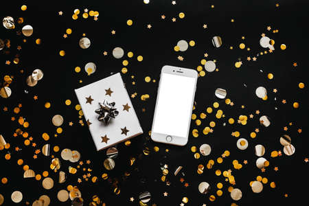 Cell phone with blank white screen or copy space or mockup and next to a box with a gift on a black background with gold confetti. Holiday sale conceptual background.