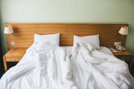 View of a rumpled bed with white pillows and a duvet.