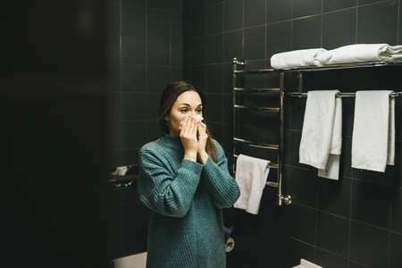 The girl blows her nose into a handkerchief. She is sick or allergic.