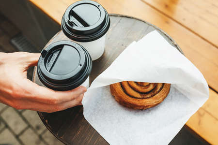 Takeaway food - coffee and a bun on a street table.