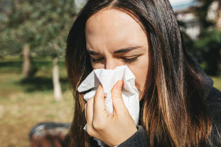 The woman blows her nose into a handkerchief. A symptom of an illness or allergy Standard-Bild