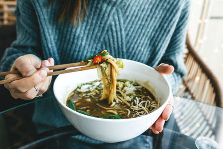 Close-up of a girl eating with chopsticks from plates of ramen noodle soup. Asian traditional food.