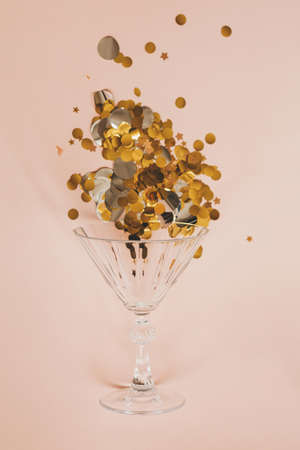 Wine glass with gold sparkles or confetti on a pink background. Celebration concept. Standard-Bild