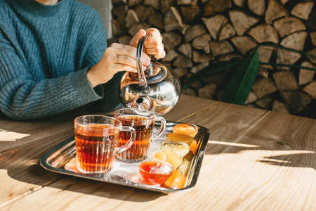 The person drinks tea with food and jam. Tea ceremony or relaxation. Delicious breakfast food. Rustic style.