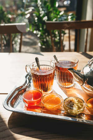 Tea and jam on a wooden table. Rustic breakfast.