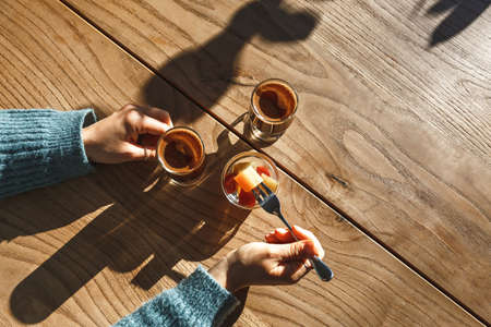The girl drinks coffee and eats sweets during a coffee break or rest.