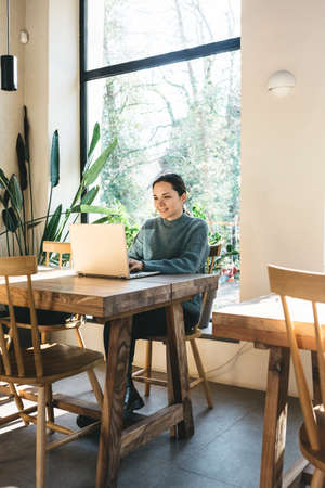 A beautiful young girl student or freelancer uses a laptop. She is studying or working remotely. Standard-Bild