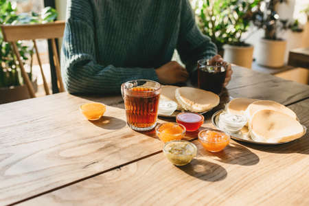 Delicious morning food with pancakes and tea with jam on a wooden table. The girl eats and drinks tea.