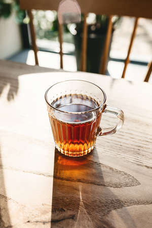A mug of tea on a wooden table in a rustic style. Standard-Bild