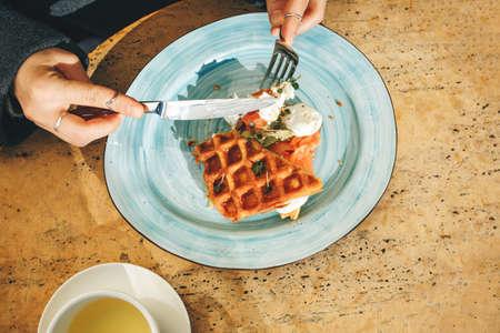 Close-up. Woman eats Belgian waffles for breakfast