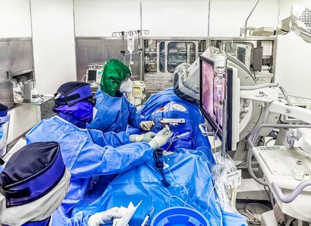 This shot shows an ongoing emergency coronary angioplasty procedure perform in a cardiac catheterization laboratory during COVID. The medical staff is in full PPE.