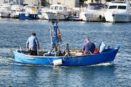 Two fishermen on a motor boat fall in the port of Mola di Bari