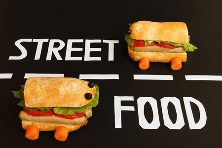 like english: two sandwiches shaped like  a car race in the two lanes of a street where  are placed  the letters  of white colour  that form the written english  street food Stock Photo
