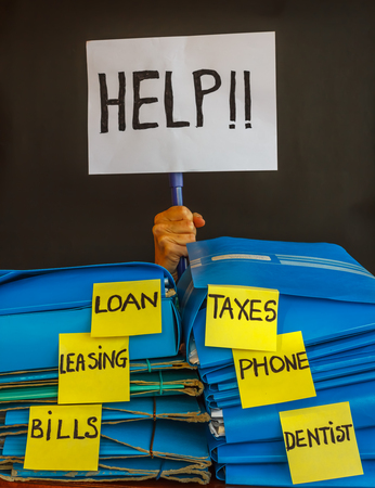payable: the hand of a person holding a sign  reading help appears behind a stack  of folders that contain  accounts payable Stock Photo