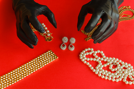 lustful: two hands wrapped in black gloves are going to steal  a set  of necklaces,bracelets and  earrings of gold  and diamonds  placed on a red background Stock Photo