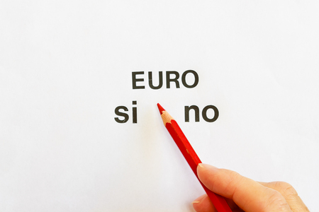 denial: the hand of a person is going to express their vote on the approval or denial of the use of the euro as a currency