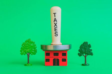 a meat mallet with the word taxes compresses a crushing home, representing the tax burden that exists on the house Stock Photo
