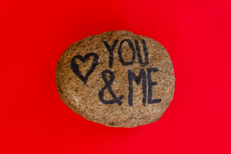 the writing you and me with a heart drawn on a stone,indicates the love promise of two lovers Stock fotó