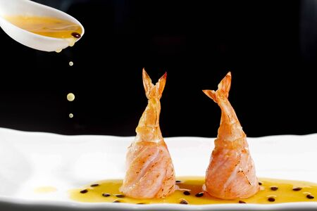 Japanese food salmon and shrimp, with passion fruit sauce beautiful drops. Asian cuisine, oriental distinct fusion served on white plate, dark background, macro view.