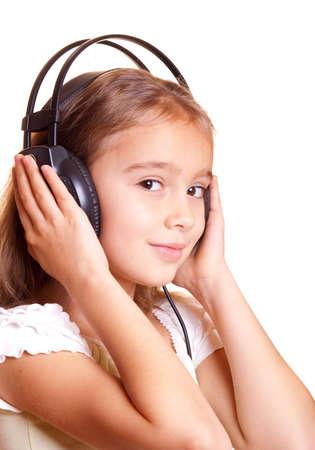Cute little girl listening music in headphones photo