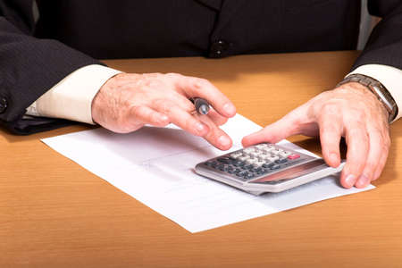 man hand holding pen on calculator buttons in office photo
