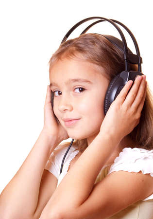 Cute little girl listening music in headphones photo