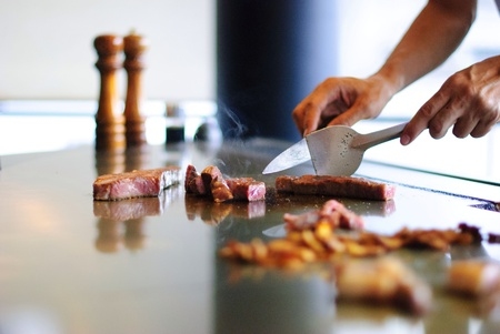 A chef at Misono handling the Kobe beef on the teppan. Stock Photo