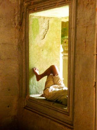 Man resting in a window, Ankor Wat, Cambodia