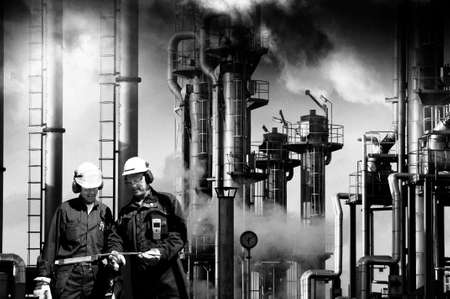 two refinery workers with industrial plant in background
