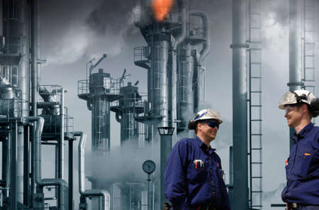 two oil and gas workers inside refinery, flames and fire from chimneys