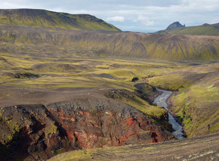 Laugavegur hike in Iceland green tuff hills and stream.