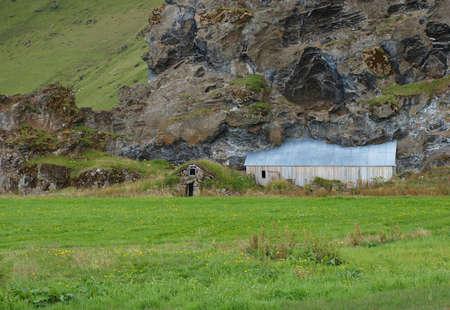 Abandonned farm under a lava rock face, Iceland.