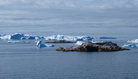 icefjord: Icebergs west of Ilulissat town, with a small fishing boat next to anl island.