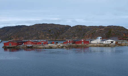 Red and white buildings of a greenlandic fishery on a small island next to the shore. Stock Photo