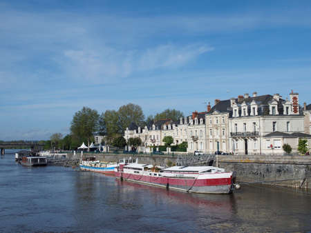 Docks, Angers center in front of the medieval castle with white tuff buildings and barges          Stock Photo