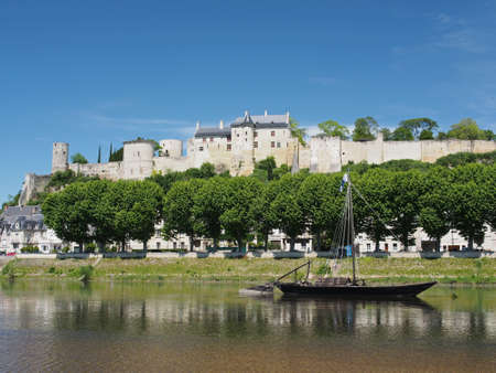 Gabare in front of the city and medieval fortress of Chinon, France.