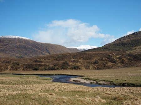River Affric in Glen Affric, with snow covered moutains, Scotland in may.