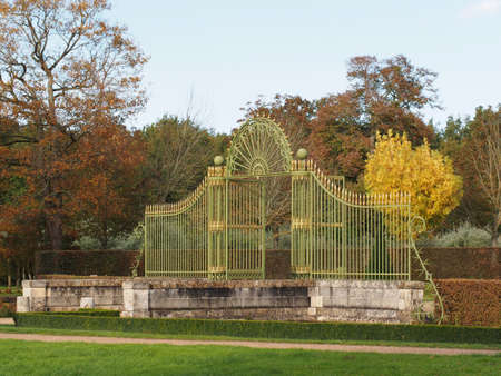 Green and gold gate behind a stone bridge, with autum colored trees in the background. Stock Photo - 16110739