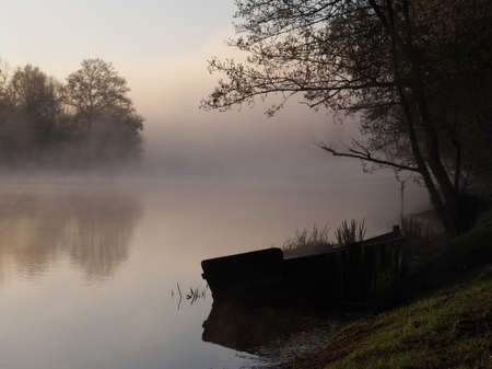 small boat on the bank of the canal with early morning mist      Stock Photo