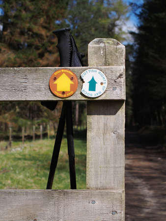 Wooden fence with hiking poles and scottish right of way sign        Editorial