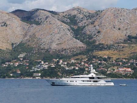 Yacht with Crotia coast north of Cavtat in the background Stock Photo
