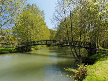 Metallic footbridge on the Indrois river in spring, France