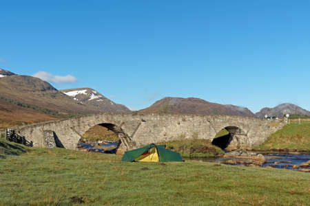 Tent by Spey river at Garva bridge with Creag Liath and Creag Chathalain in the background, Scotland in spring