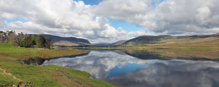 Spey river west of the dam with hills and clouds reflections , Scotland in spring