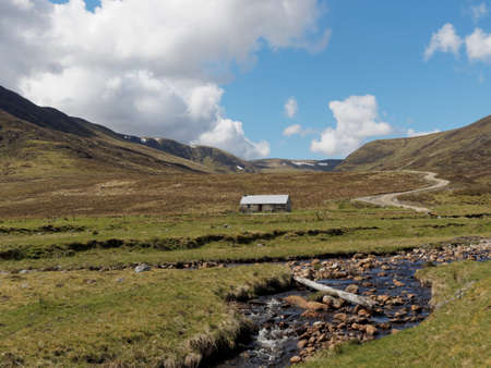 River Calder, Glen Banchor bothy west of Newtonmore, with hills and track in the background Stock Photo