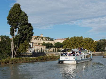boat on the midi canal, with Beziers old town in the background, France.