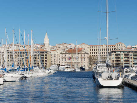Marseille city hall seen from across the harbor with boats in the foreground, France