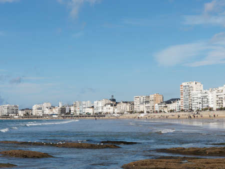Les Sables dOlonne, seafront a sunny day in autumn, white buildings and crescent form sand beach, France