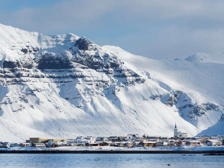 Grundarfjordur small coastal town in Snæfellsnes peninsula north side, Iceland, with snow covered mountains in the background.