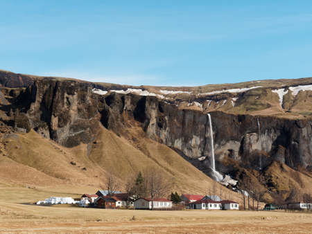 Basalt cliff, Foss a Sidu waterfall and farm, with blue sky in winter seen from road 1, southern Iceland Reklamní fotografie